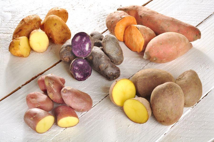 Assorted Potatoes on Wood Background