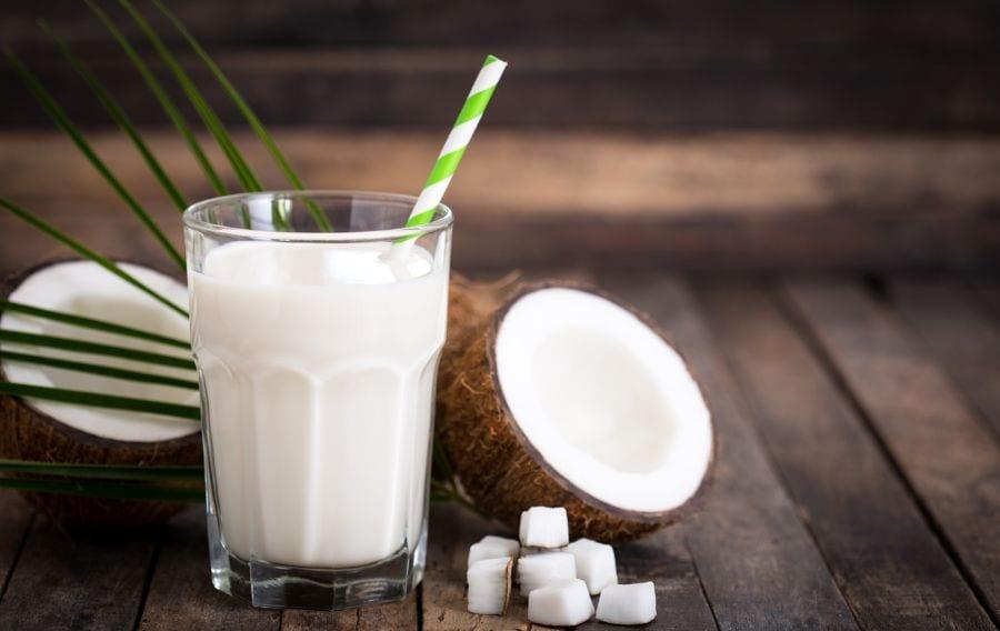 Coconut Milk in a Glass Near Coconuts
